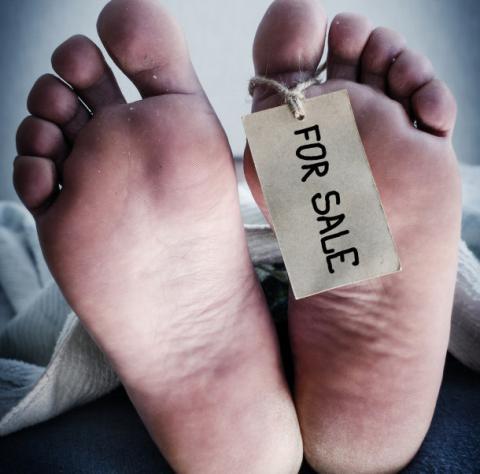 Zwei Füße mit den Schild For Sale